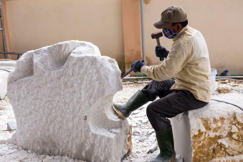 Masque respiratoire de port de travailleur vietnamien sculptant le gros morceau énorme du marbre photos stock