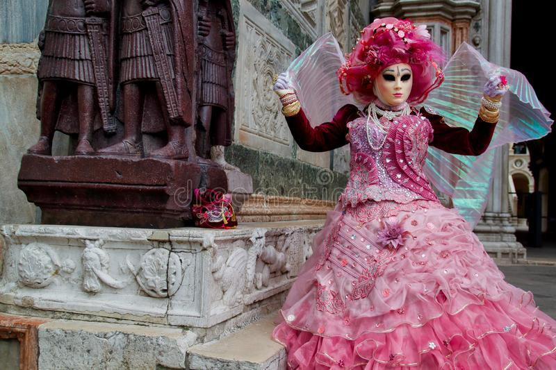 Masque rosa-rose et costume de carnaval coloré au festival traditionnel à Venise, Italie image stock