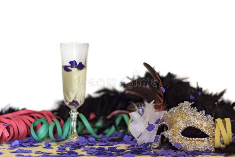 Masque, serpentines, confettis et verre de carnaval de champagne Fond coloré de partie avec l'espace de copie photo libre de droits