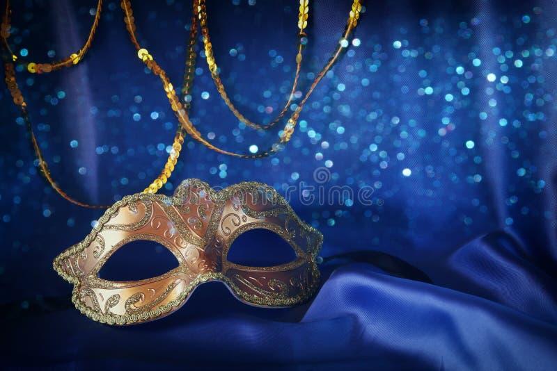 masque vénitien d'or sur le fond en soie bleu photo stock