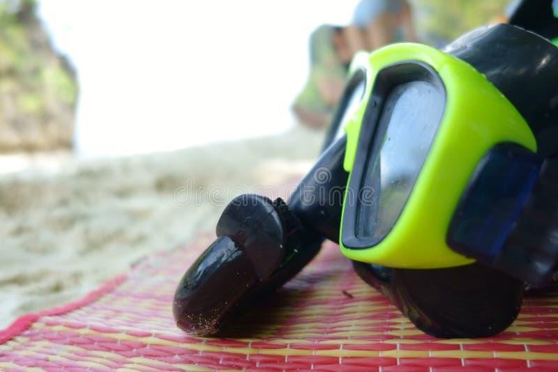 Masque vert de prise d'air et de plongée sur le tapis à la mer photographie stock