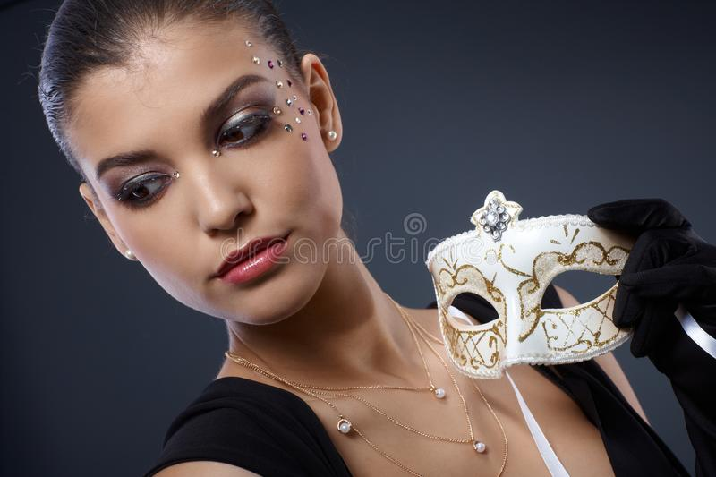 Masquerade elegance. Of attractive woman wearing glamorous makeup with strasses, holding fancy carnival mask royalty free stock photo