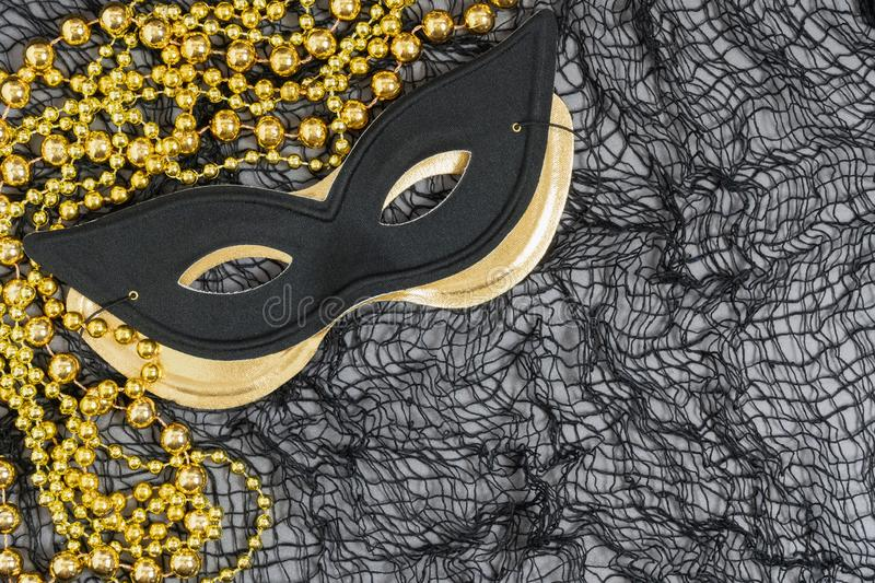 Masquerade or Halloween background with a black cat style mask. And a metallic gold mask and golden beads on a netting background stock image