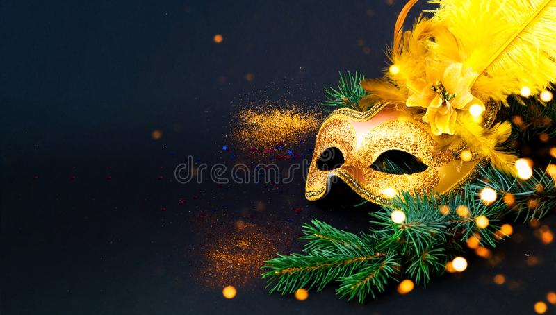 Masquerade mask on black background with confetti. New Years decor. Blurred effect. Close-up, copy space stock photos