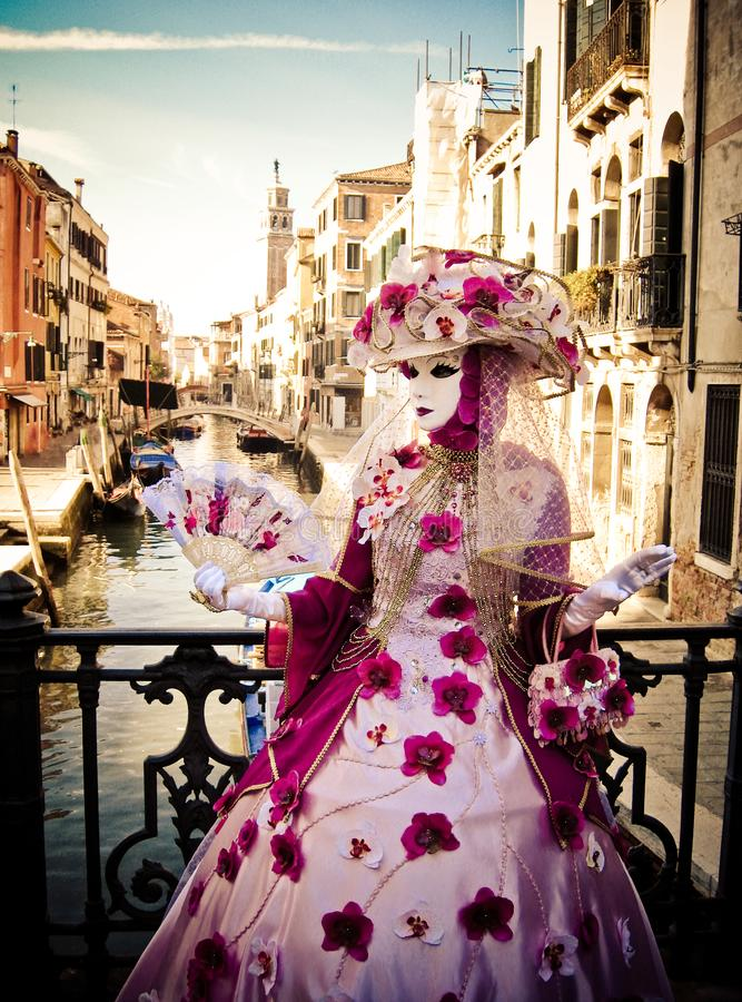 Masquerade in Venice. In rich exquisite costumes and masks, fan, hat with flowers, Italy, carnival royalty free stock image