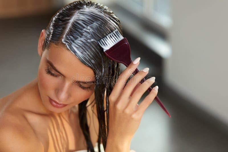 Masques de cheveux Femme appliquant le masque avec la brosse sur de longs cheveux humides photo libre de droits