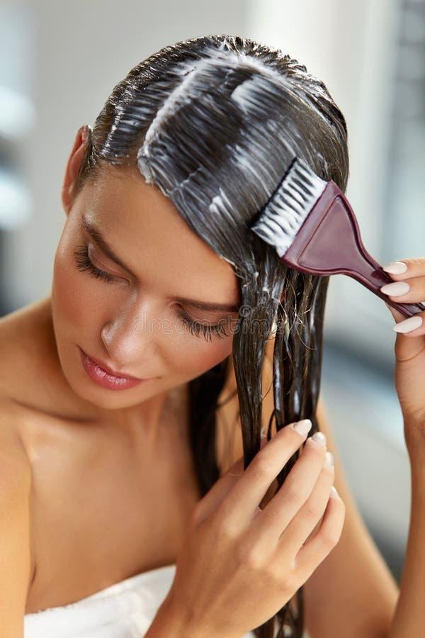 Masques de cheveux Femme appliquant le masque avec la brosse sur de longs cheveux humides photo stock