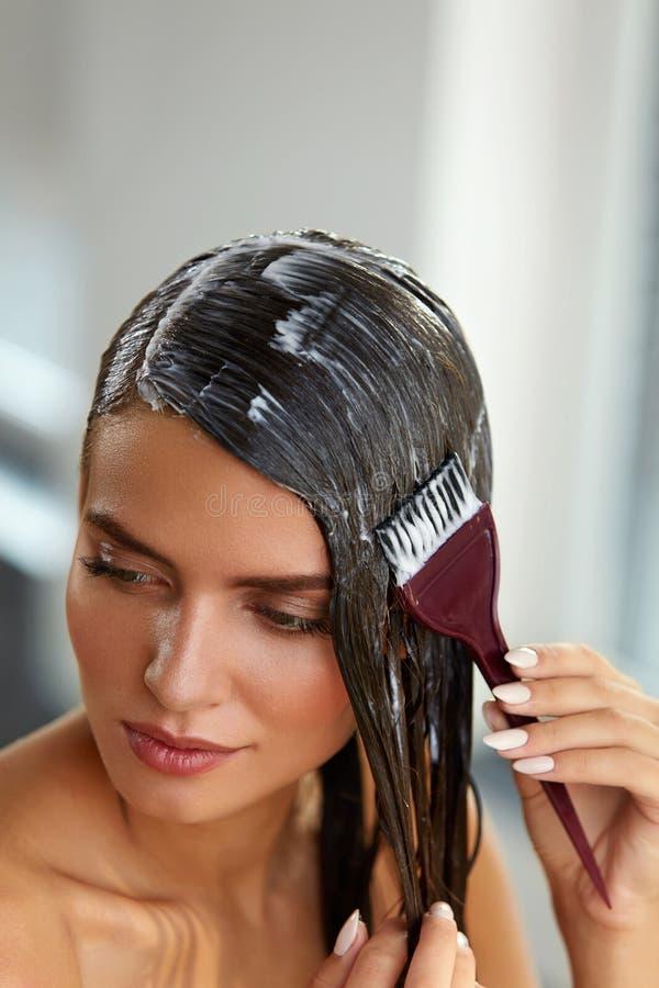 Masques de cheveux Femme appliquant le masque avec la brosse sur de longs cheveux humides images libres de droits