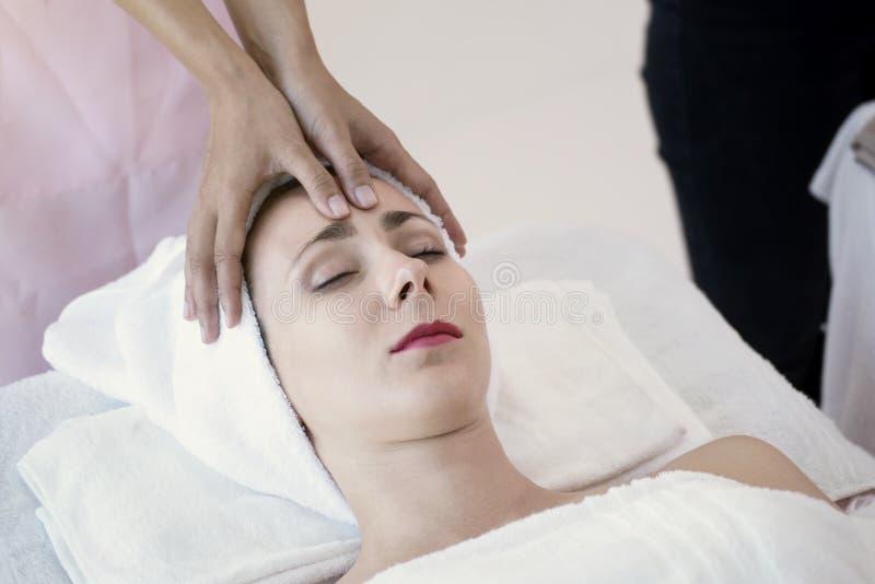 Massör som gör massage huvudet av härligt koppla av för ung kvinna fotografering för bildbyråer