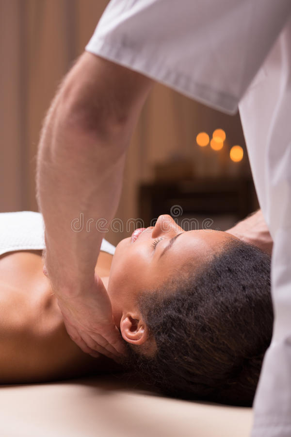 Massör som masserar den härliga afroamerican kvinnan royaltyfri fotografi