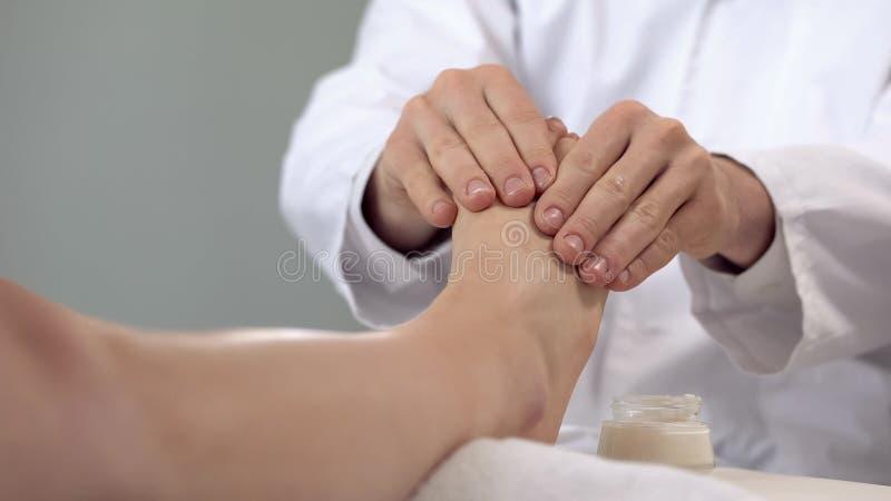 Massören som applicerar massera kräm till patienter, lägger benen på ryggen, avslappnande tillvägagångssätt, hälsa royaltyfri foto