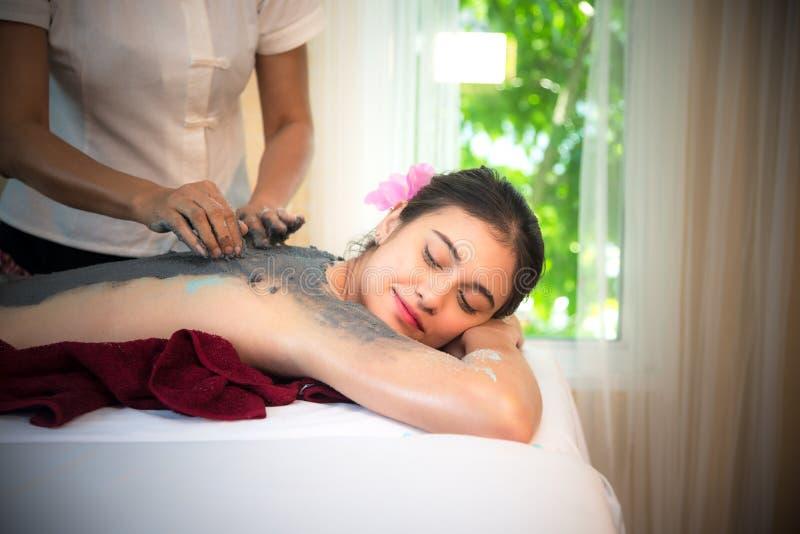 Massören som gör massagebrunnsorten med behandlinggyttja på asiatisk kvinnakropp i den thailändska brunnsortlivsstilen, så koppla arkivfoton
