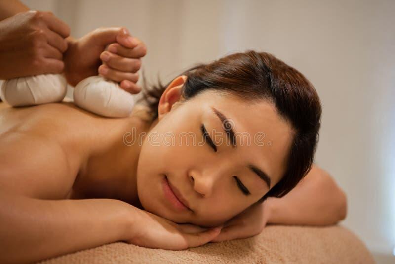 Massös som gör massage på asiatisk kvinnlig kropp i brunnsortsalongen royaltyfria foton