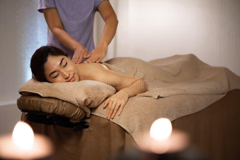 Massös som gör massage på asiatisk kvinnlig kropp i brunnsortsalongen fotografering för bildbyråer