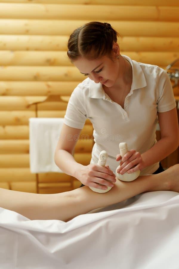 Massös som gör thai massage med salta påsar royaltyfri foto