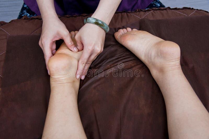 Massösen gör massage på foten för kvinnlig kund royaltyfria foton