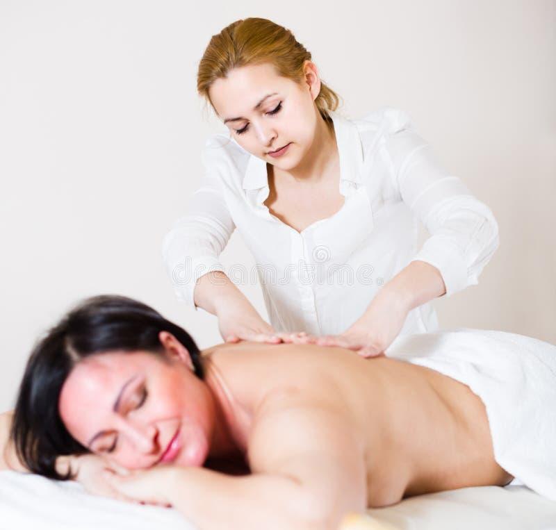 Massösen gör sund massage av baksida och fransyskan till den vuxna womaen arkivbilder