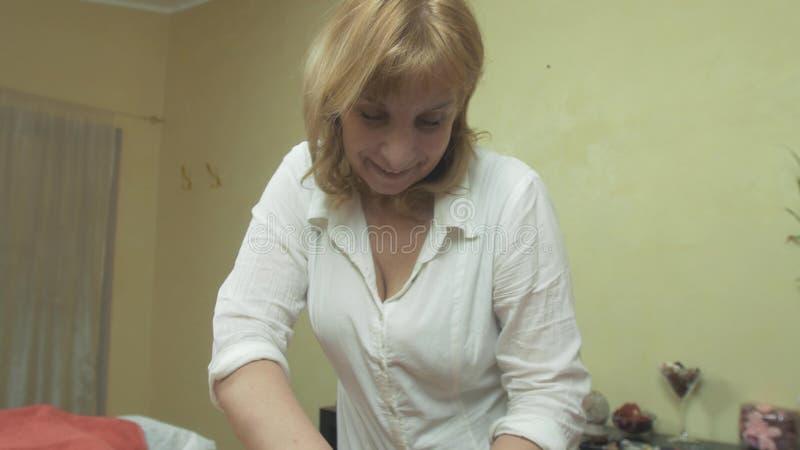 Massösen gör yrkesmässig massage av tillbaka till den unga kvinnan i salong pressing stock video
