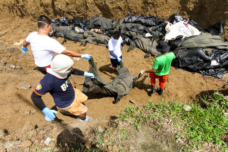 Mass grave for victims of typhoon Haiyan in Philippines. Tacloban City, Philippines- November 17, 2913:A total of 393 cadavers, in black bags, were laid in a stock image