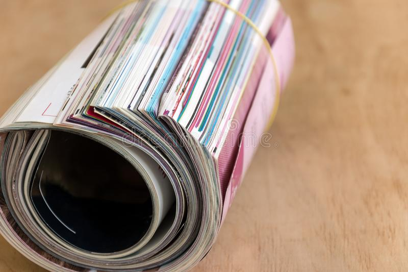 Roll of glossy colorful magazines on wooden background. stock image