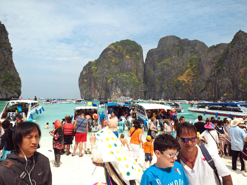 Mass tourism on Maya beach Thailand. MAYA BAY, THAILAND - FEBRUARY, 2015: Crowds of visitors enjoy a day trip at Maya Bay, one of the iconic beaches of Phi Phi stock photography