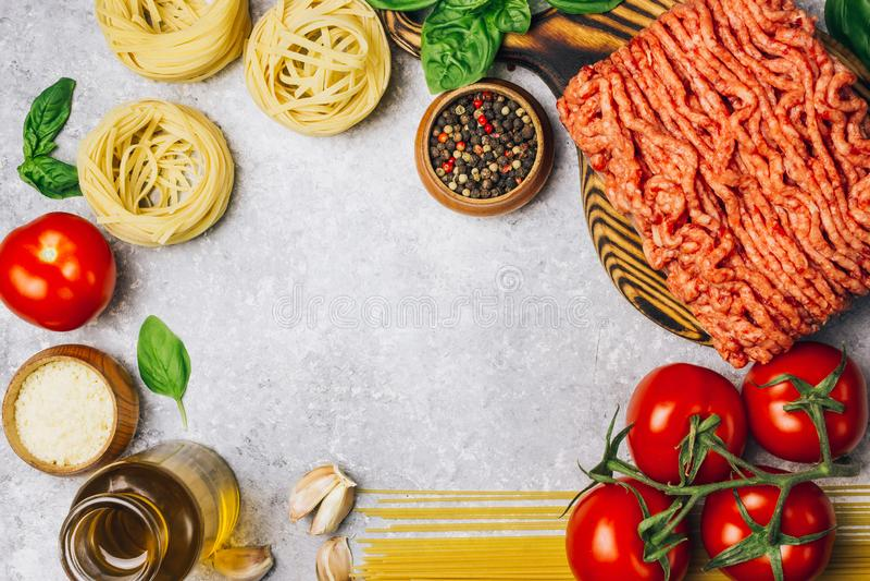 Massa bolonhesa que cozinha o conceito: carne triturada crua, tomates, massa, Parmesão, alho, manjericão, azeite fotos de stock royalty free