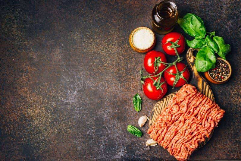 Massa bolonhesa que cozinha o conceito: carne triturada crua, tomates, massa, Parmesão, alho, manjericão, azeite foto de stock