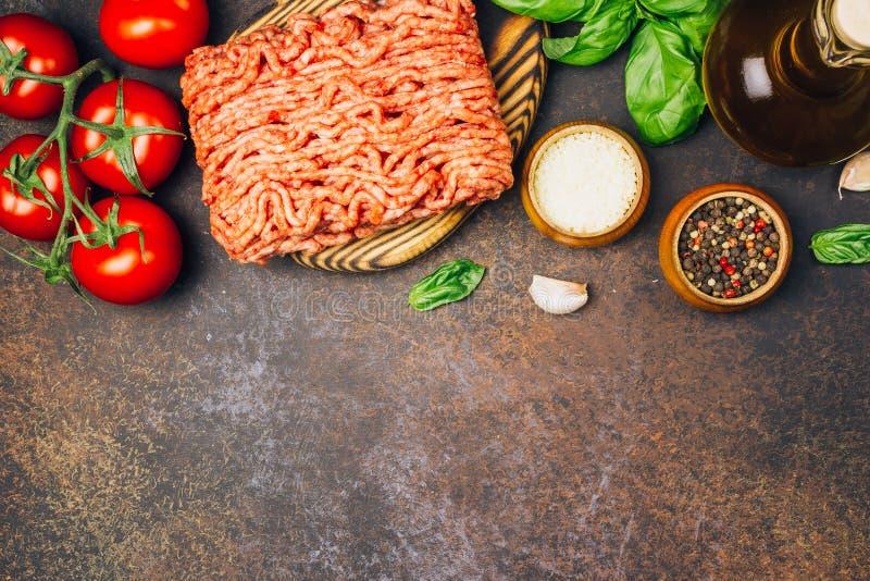 Massa bolonhesa que cozinha o conceito: carne triturada crua, tomates, massa, Parmesão, alho, manjericão, azeite imagem de stock