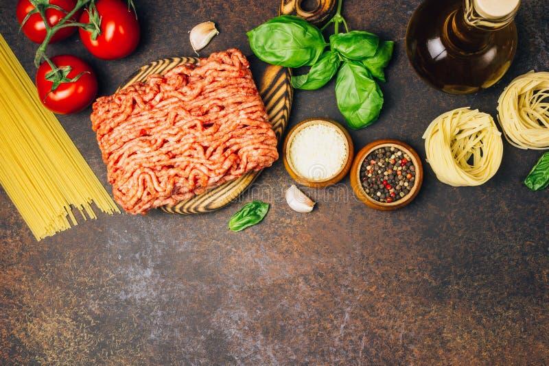 Massa bolonhesa que cozinha o conceito: carne triturada crua, tomates, massa, Parmesão, alho, manjericão, azeite imagens de stock