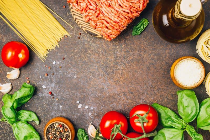 Massa bolonhesa que cozinha o conceito: carne triturada crua, tomates, massa, Parmesão, alho, manjericão, azeite fotografia de stock