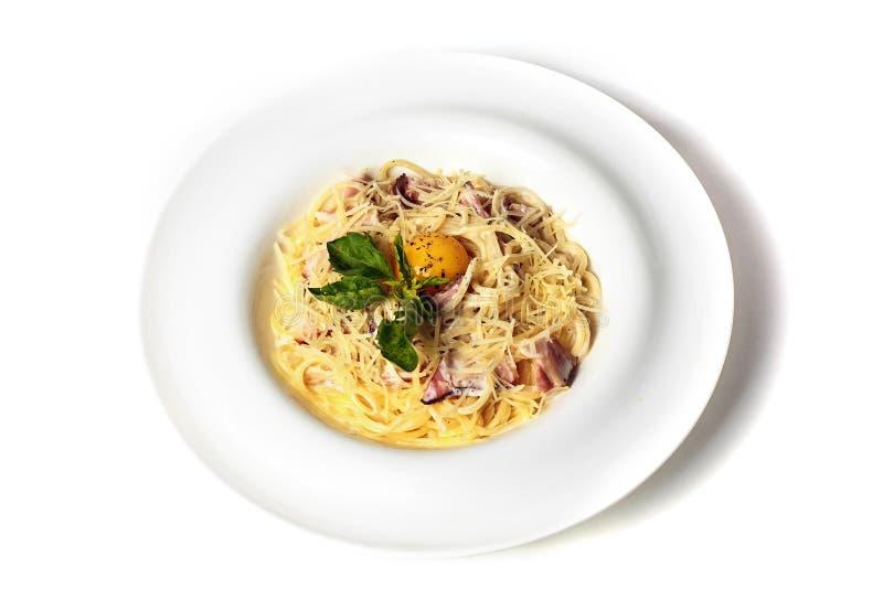 Massa Carbonara com bacon, manjericão, ovo e queijo Isolado no fundo branco Vista superior fotos de stock royalty free