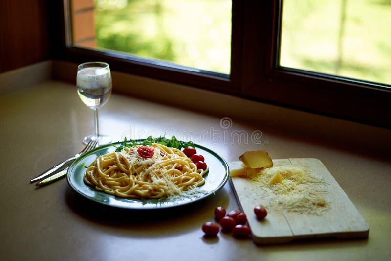 Massa Carbonara com os tomates raspados do queijo parmes?o e de cereja, decorados com r?cula Almo?o italiano foto de stock