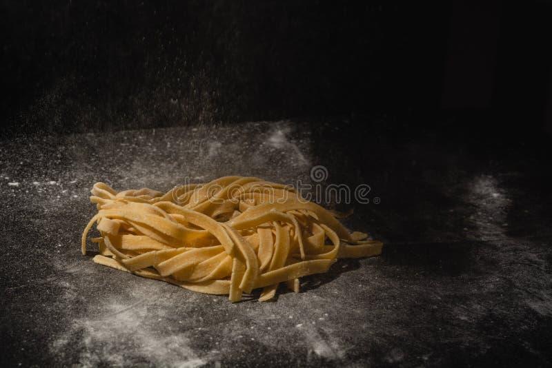 Massa caseiro cru italiana fresca M?os que fazem a massa espaguete Espaguetes italianos frescos Close up do processo de fatura fotos de stock royalty free