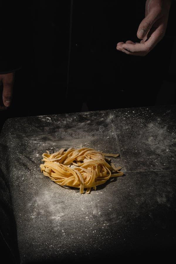 Massa caseiro cru italiana fresca M?os que fazem a massa espaguete Espaguetes italianos frescos Close up do processo de fatura fotografia de stock
