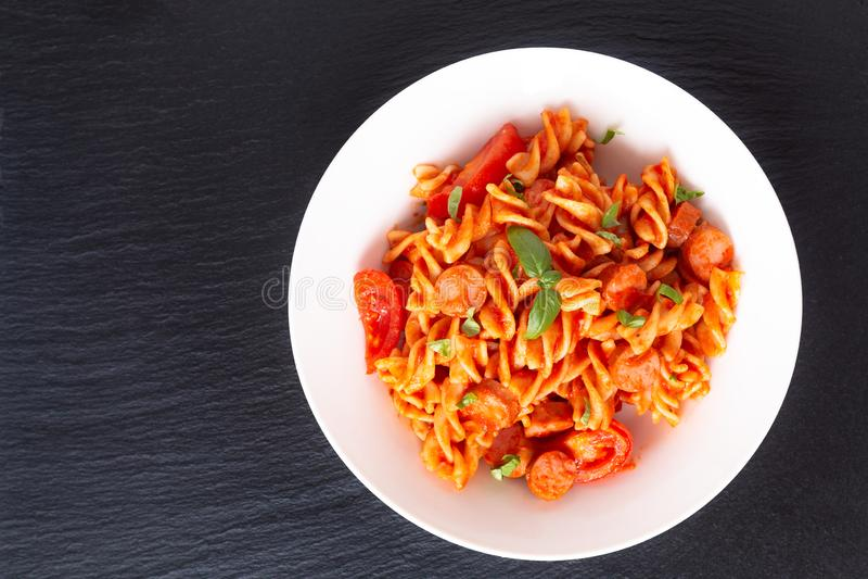 Massa caseiro de Fusilli do conceito do alimento com molho de tomate em um prato branco no fundo preto da pedra da ardósia fotografia de stock royalty free
