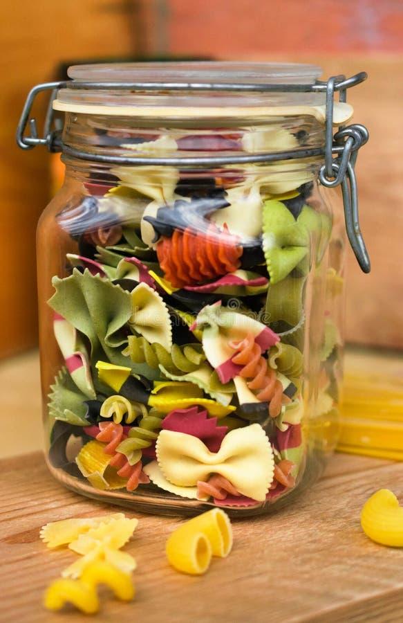Massa colorida no frasco de vidro na tabela de madeira fotografia de stock