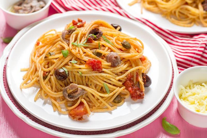 Massa com o alla dos espaguetes dos tomates, das azeitonas, das alcaparras e das anchovas fotografia de stock royalty free