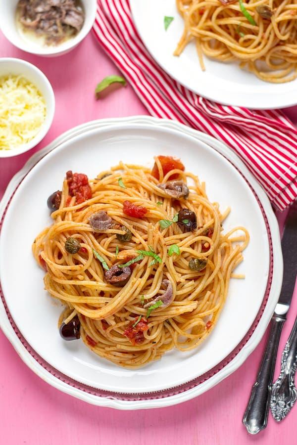 Massa com o alla dos espaguetes dos tomates, das azeitonas, das alcaparras e das anchovas imagem de stock
