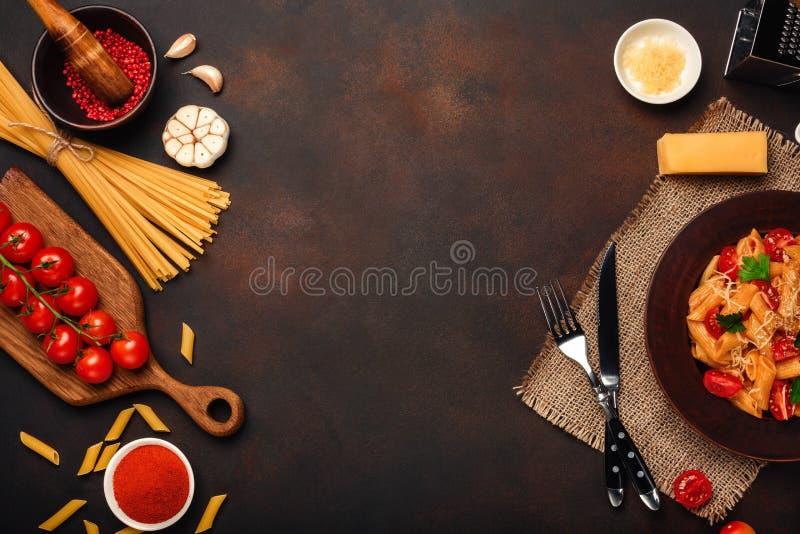 Massa com queijo, molho de tomate da cereja, pimenta, alho, cúrcuma no fundo oxidado imagens de stock royalty free