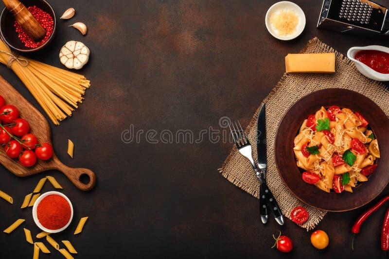 Massa com queijo, molho de tomate da cereja, pimenta, alho, cúrcuma no fundo oxidado imagem de stock royalty free