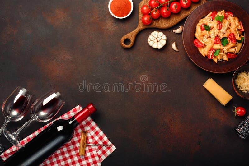 A massa com queijo, o molho de tomate da cereja, o copo de vinho e a garrafa wine, o alho, cúrcuma no fundo oxidado fotografia de stock royalty free