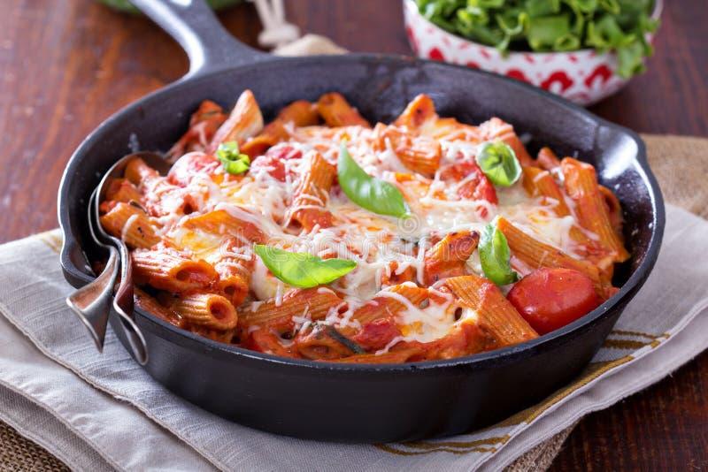 A massa coze com penne, tomates e mozarella fotografia de stock