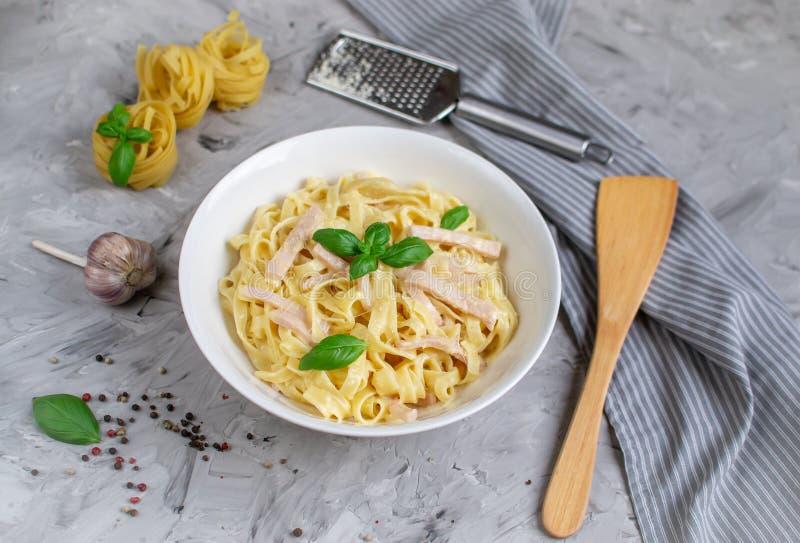 Massa cozinhada dos tagliatelle em uma placa com molho de Carbonara, bacon, manjericão e queijo parmesão, alimento de Itália imagens de stock