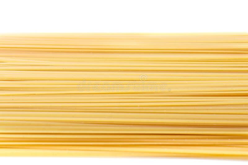 Massa cru dos espaguetes, em um fundo branco Macarronetes crus do espaguete Produtos secos da farinha foto de stock royalty free