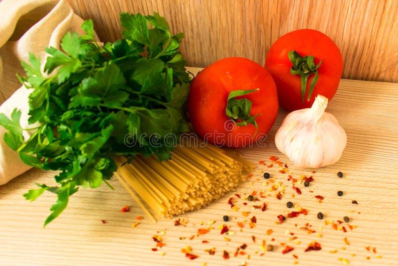 Massa crua com tomates e especiarias e ervas na tabela imagem de stock