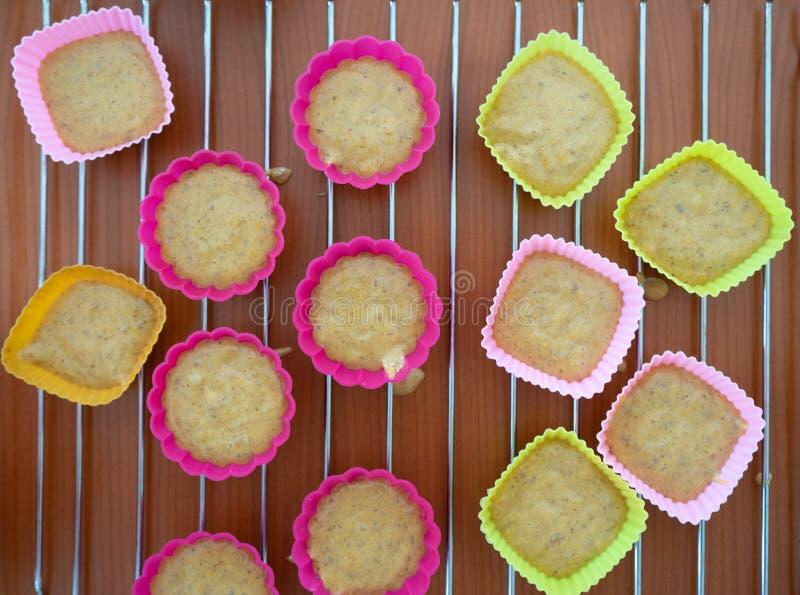 Massa crua do bolo em moldes do silicone em uma bandeja de cozimento O processo de fazer queques Queques caseiros da ab?bora fotografia de stock