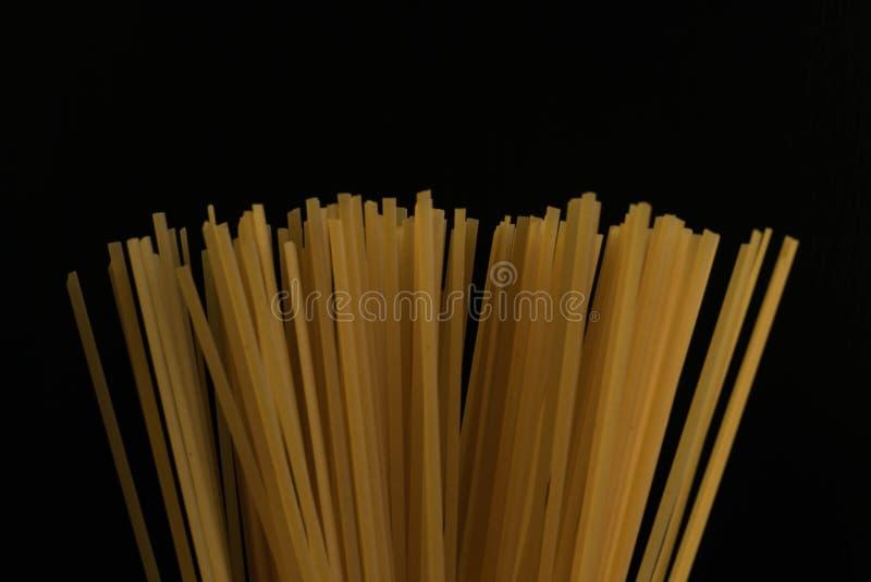 Massa crua dos espaguetes italianos, fundo escuro fotos de stock royalty free