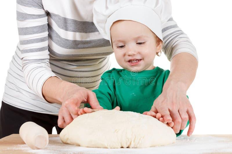 Massa de amasso de sorriso do rapaz pequeno para as cookies, isolada no branco imagens de stock
