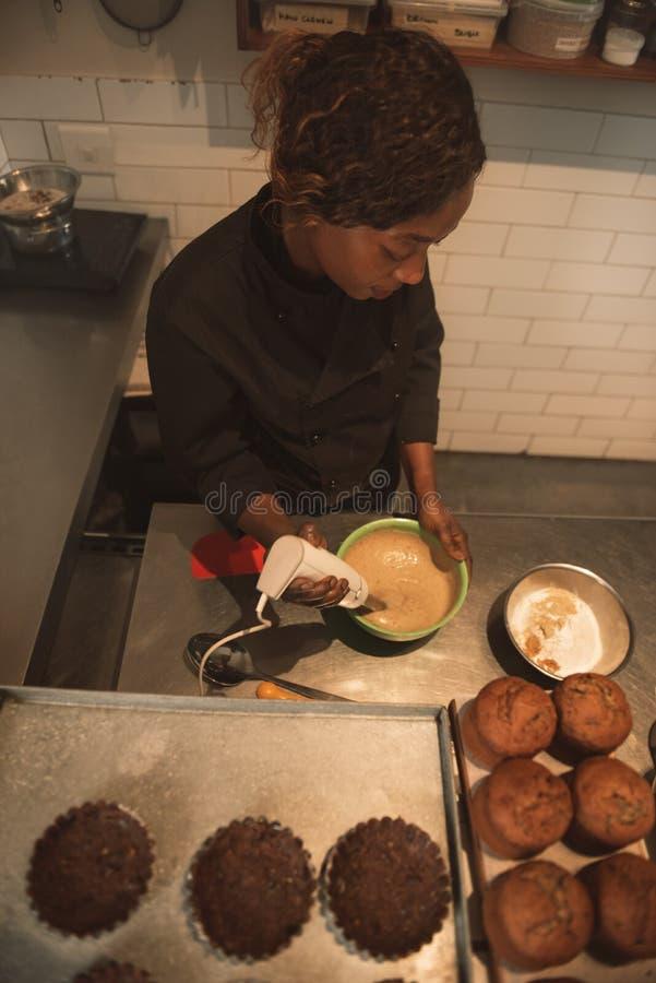 Massa de bolo de mistura do padeiro em uma cozinha comercial foto de stock royalty free