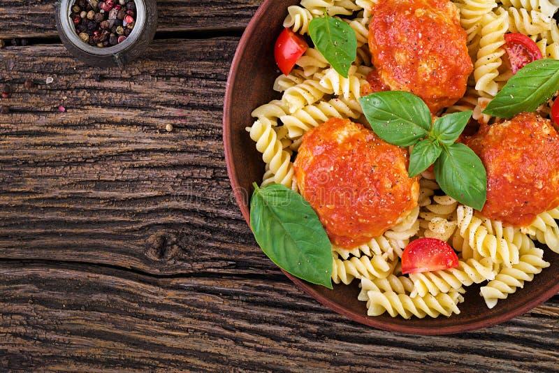 Massa de Fusilli com as almôndegas no molho de tomate e a manjericão na bacia imagem de stock